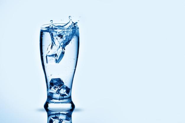 Os cubos de gelo lambendo em copo de água.