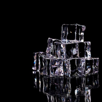 Os cubos de gelo são dispostos em um slide, isolados em um fundo preto.