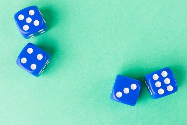 Os cubos de jogo de cor azul encontram-se em uma superfície brilhante monocromática.
