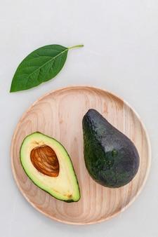 Os cuidados com a pele alternativos e esfregam o abacate fresco no fundo de mármore.