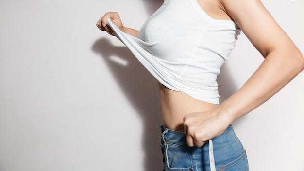 Os cuidados médicos e a mulher fazem dieta o conceito do estilo de vida para reduzir a barriga e dar forma ao músculo saudável do estômago.