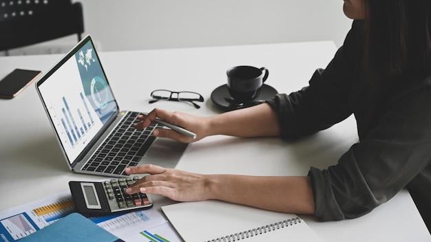 Os dados novos da análise da mulher de negócios do close up no laptop e calculam na calculadora.