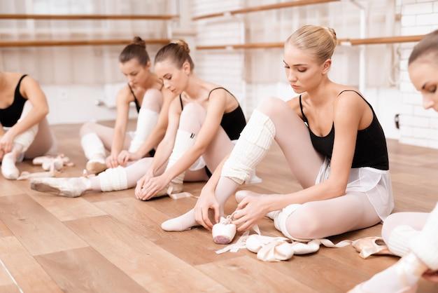 Os dançarinos de balé das moças ensaiam na classe do bailado.