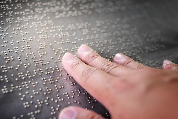 Os dedos cegos tocando as letras em braille na placa de metal