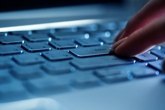 Os dedos da mulher no teclado do laptop no escritório