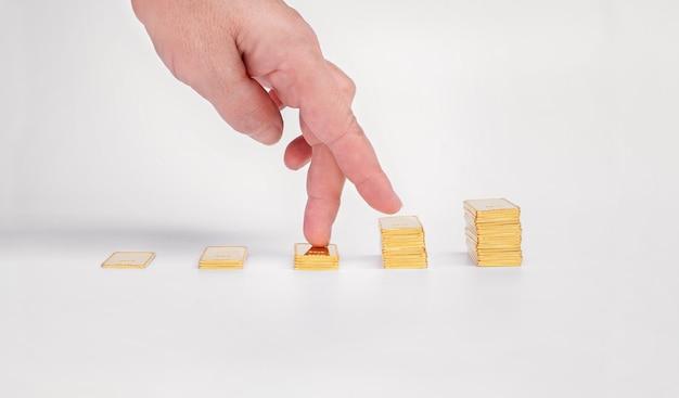Os dedos das mulheres sobem na escada de barras de ouro. lingote de ouro em uma superfície leve