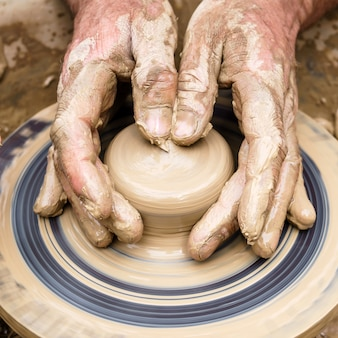 Os dedos de potter tocam o pedaço informe de argila na roda giratória, dando-lhe forma
