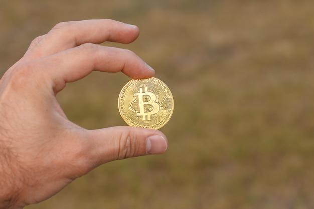 Os dedos do homem estão segurando uma grande moeda de bitcoin dourada redonda