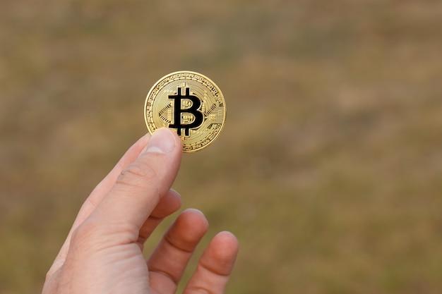 Os dedos do homem estão segurando uma moeda grande e redonda de bitcoin dourado na frente do padrão verde amarelo.