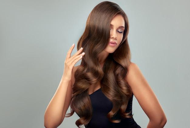 Os dedos graciosos da mulher tocam suavemente os cachos perfeitos do seu cabelo comprido denso e bem cuidado penteado elegante à noite para cabelos longos, manicure elegante nas unhas e maquiagem elegante retrato de mulher