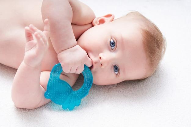 Os dentes do bebê estão sendo cortados. garoto bonito com olhos azuis mordisca um brinquedo.