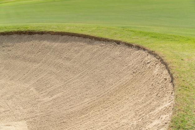 Os depósitos bonitos lixam e grama verde no campo do golfe.