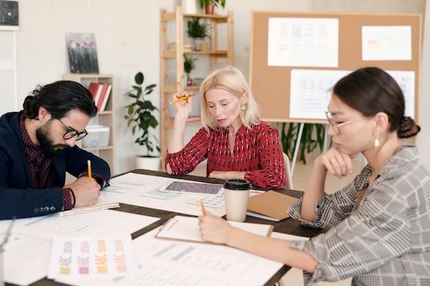 Os designers criativos fazem um brainstorming enquanto trabalham individualmente em um ambiente de escritório contra prateleiras com plantas e quadro com esboços