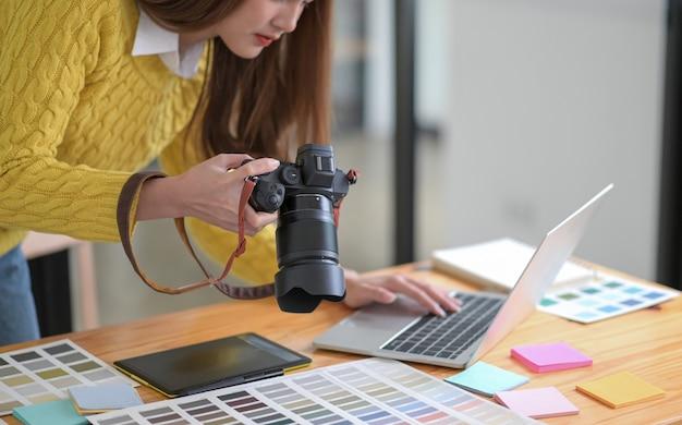 Os designers estão olhando as fotos da câmera e usando um laptop.