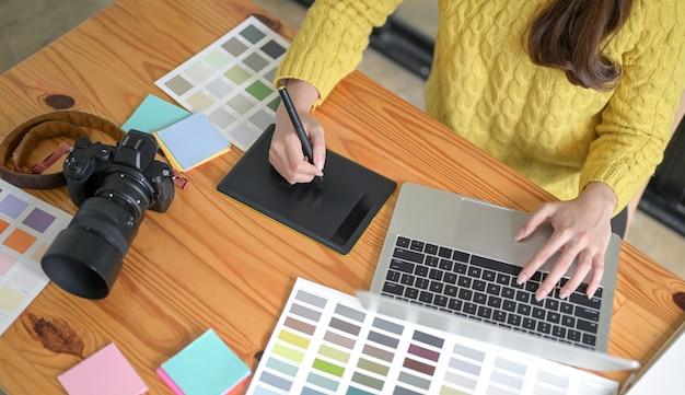 Os designers estão trabalhando em um tablet e laptop de desenho.