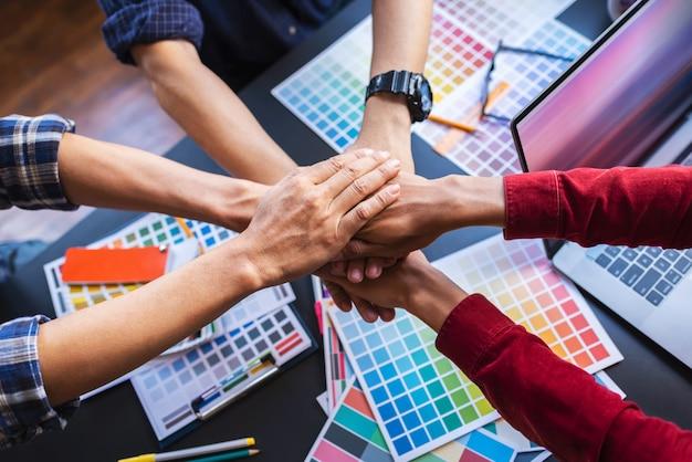 Os designers gráficos dos povos asiáticos juntam-se à mão, conceito dos trabalhos de equipa após a reunião.