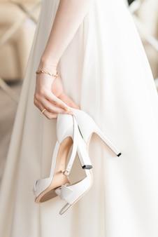 Os detalhes do dia do casamento. sapatos nas mãos da noiva