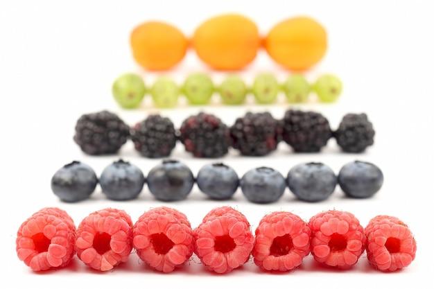 Os diferentes tipos de bagas encontram-se em filas sobre fundo branco. vitamina útil comida saudável