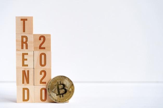 Os dígitos 2020 e a palavra tendência em cubos de madeira em um fundo branco ao lado de uma moeda de bitcoin.
