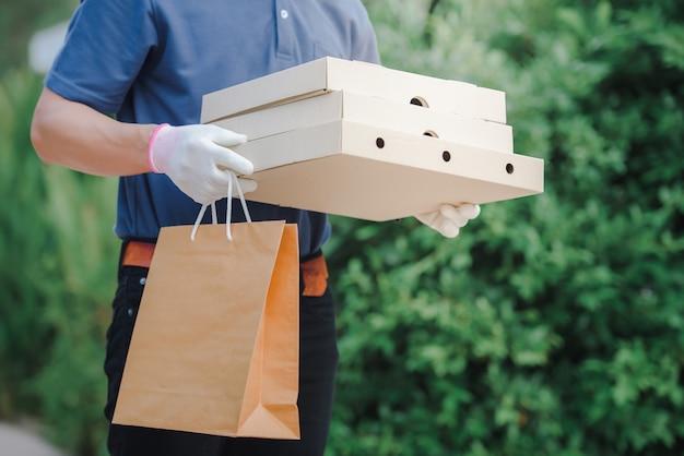Os distribuidores asiáticos usam máscaras protetoras e luvas médicas para entrega on-line. serviço de entrega em domicílio em condições de quarentena do surto do vírus da doença coronariana-19