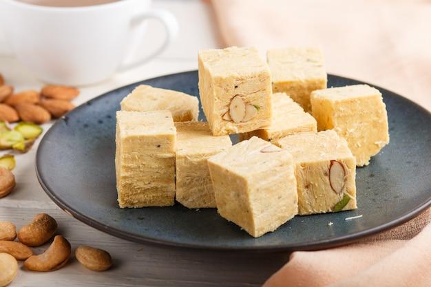 Os doces indianos tradicionais soan papdi em uma placa cerâmica azul com amêndoa, pistache e uma xícara de café em um branco de madeira.
