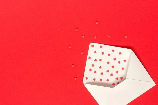 Os doces vermelhos polvilham corações dos doces voam fora do envelope do livro branco no fundo vermelho.