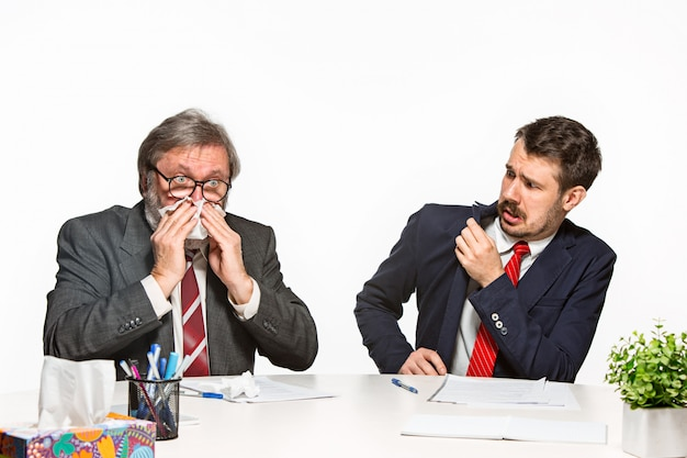 Os dois colegas que trabalham juntos no escritório em fundo branco.