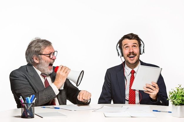 Os dois colegas trabalhando juntos no escritório em fundo branco. um homem gritando em um megafone - o outro em fones de ouvido não consegue ouvir nada