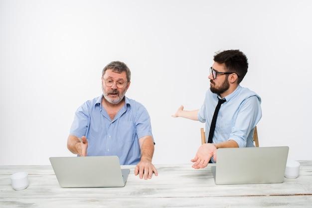 Os dois colegas trabalhando juntos no escritório na parede branca
