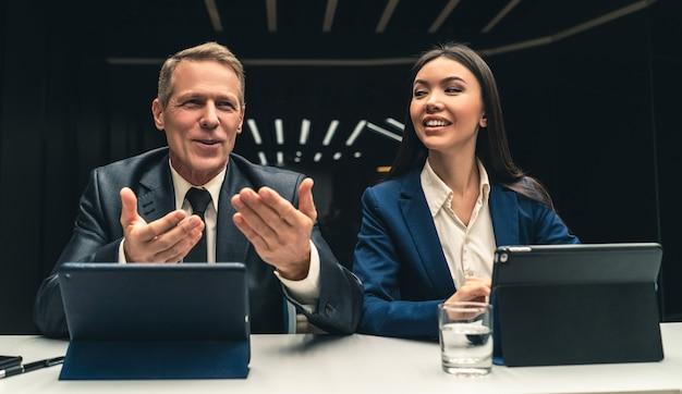 Os dois empresários sorridentes sentados à mesa