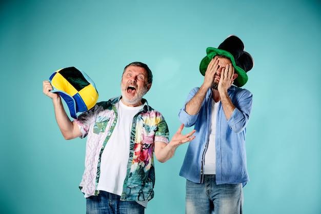Os dois fãs de futebol sobre o azul