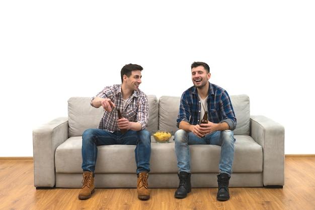 Os dois homens bebem uma cerveja com batatas fritas no sofá sobre um fundo de parede branca