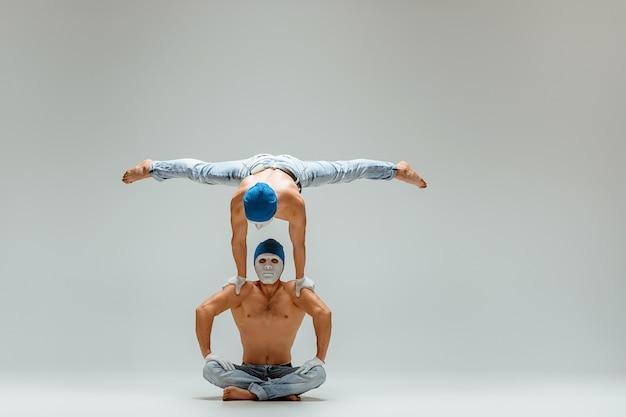 Os dois homens caucasianos acrobáticos de ginástica em pose de equilíbrio