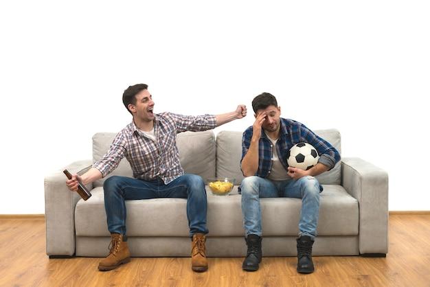 Os dois homens com um aperto de mão de cerveja no sofá no fundo branco