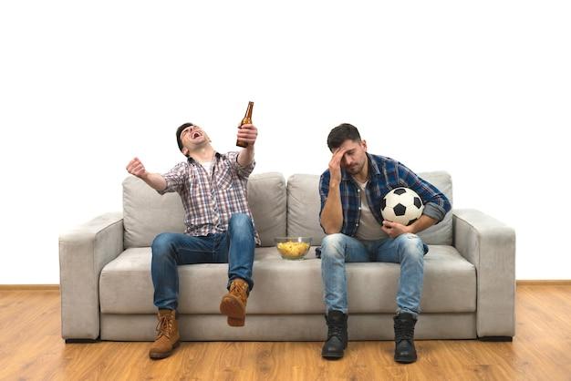 Os dois homens com uma cerveja e batatas fritas assistem a uma bola de futebol no sofá
