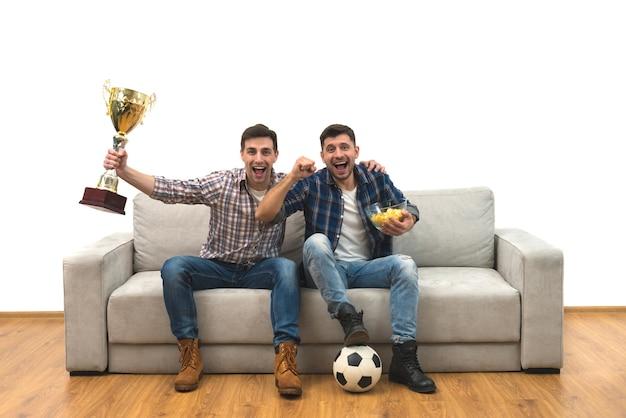 Os dois homens felizes com uma taça assistem a uma bola de futebol no sofá