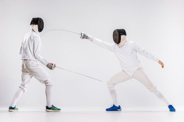 Os dois homens vestindo terno de esgrima praticando com espada contra cinza