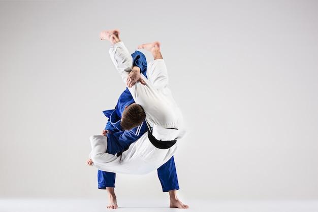 Os dois lutadores de judocas lutando contra homens