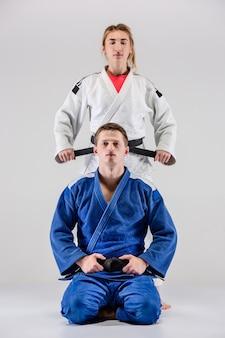 Os dois lutadores de judocas posando em cinza