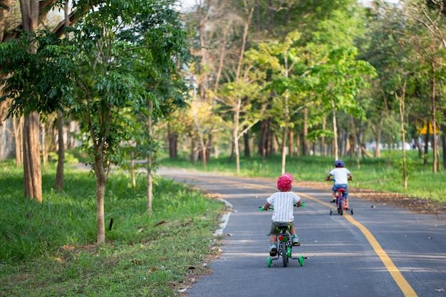 Os dois meninos adoráveis estão andando de bicicleta na bicicleta.