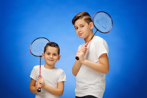 Os dois meninos com raquetes de badminton ao ar livre