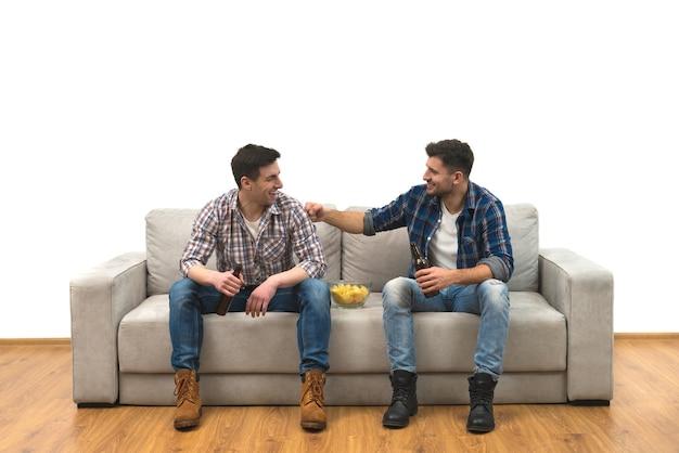 Os dois rapazes bebem cerveja com batatas fritas no sofá sobre um fundo de parede branca