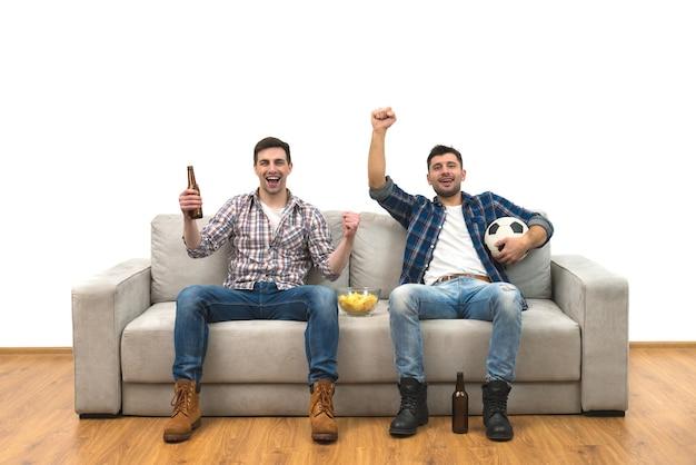 Os dois rapazes com uma cerveja assistem a uma bola de futebol no fundo de uma parede branca