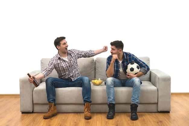 Os dois rapazes com uma cerveja assistem a uma bola de futebol no sofá sobre o fundo branco