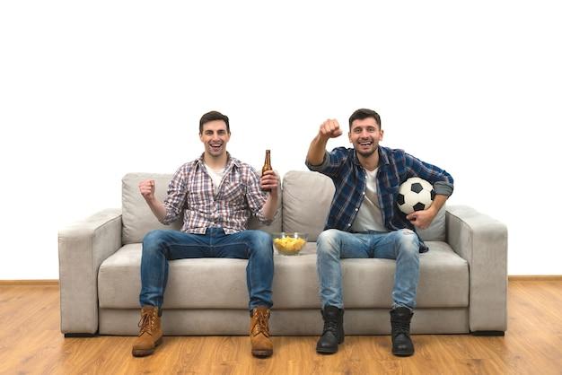 Os dois rapazes com uma cerveja assistem a uma bola de futebol no sofá