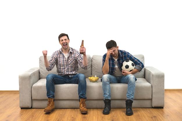 Os dois rapazes com uma cerveja e batatas fritas assistem a uma bola de futebol no sofá