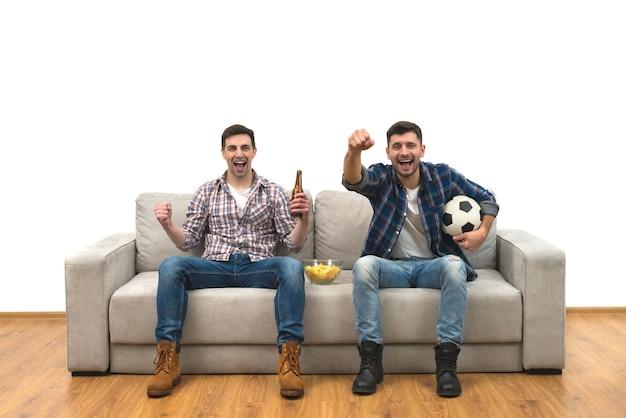 Os dois rapazes felizes com uma cerveja assistem a uma bola de futebol no sofá