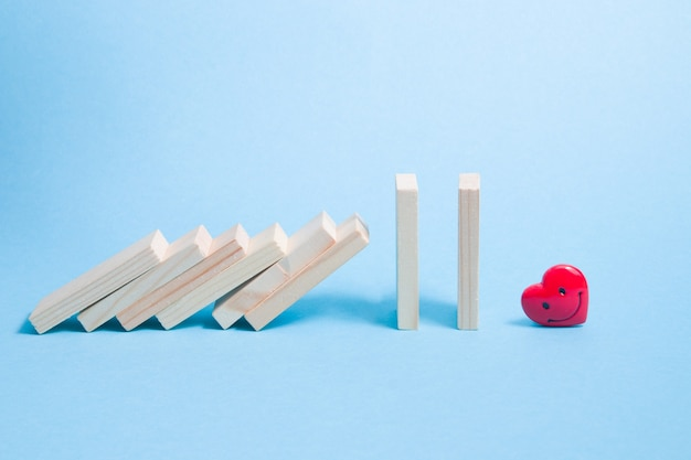 Os dominós caem na superfície do coração vermelho feliz azul claro