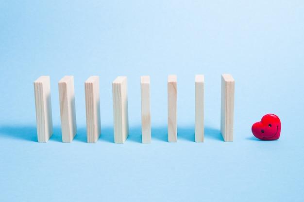Os dominós estão em uma fileira e um coração vermelho em uma superfície azul clara