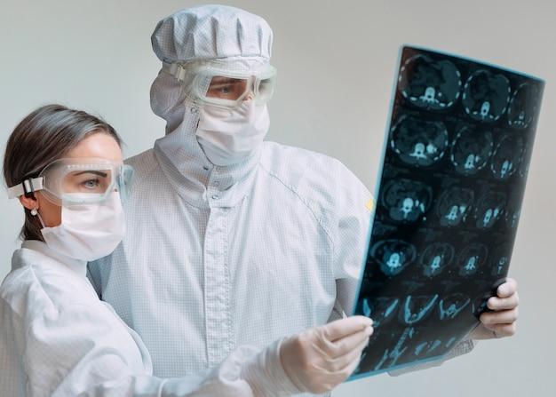 Os doutores que estão no fundo branco examinam o raio x para ver se há pneumonia de um paciente covid-19 na clínica. conceito de coronavírus.